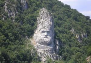 Statuia lui Decebal pe malul Dunării (Cazanale Mici). Foto: Google Street View Chipul regelui dac Decebal este un basorelief înalt de 55 m,[1] aflat pe malul stâncos al Dunării, între localitățile Eșelnița și Dubova, în apropiere de orașul Orșova, România. Basorelieful îl reprezintă pe Decebal, ultimul rege al Daciei și este sculptat într-o stâncă. Este cea mai înaltă sculptură în piatră din Europa. Omul de afaceri și istoricul protocronist Iosif Constantin Drăgan a fost cel care a promovat și finanțat ideea acestei lucrări efectuate în perioada 1994 - 2004. (Wikipedia)